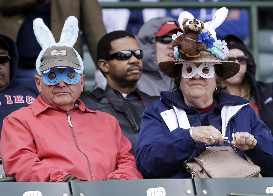 Baseball fans wearing Easter-related hats look to the field before a baseball game between the Cincinnati Reds and the Chicago Cubs in Chicago, Saturday, April 19, 2014. (AP Photo/Nam Y. Huh)