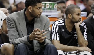 San Antonio Spurs'  Tim Duncan, left, who did not play, and Tony Parker, right, of France, sit on the bench during the first half of an NBA basketball game against the Los Angeles Lakers, Wednesday, April 16, 2014, in San Antonio. Los Angeles won 113-100. (AP Photo/Eric Gay)