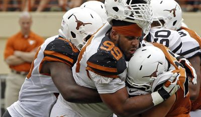 Texas defensive lineman Desmond Jackson (99) tackles Eddie Aboussie (21) with help from Steve Edmond (33) during the first half of the Orange and White spring NCAA college football game on Saturday, April 19, 2014, in Austin, Texas. (AP Photo/Michael Thomas)