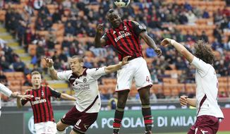 AC Milan forward Mario Balotelli, top, scores during the Serie A soccer match between AC Milan and Livorno at the San Siro stadium in Milan, Italy, Saturday, April 19, 2014. (AP Photo/Antonio Calanni)