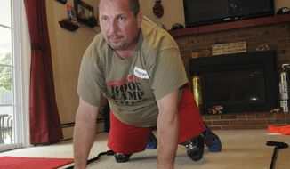 In this April 14, 2014 photo, firefighter Joe Tadijanac carefully works himself up off the ground in order to stand in his home near Mansfield, Ohio. Tadijanac, who lost both his legs while fighting a fire in June 2012, has a new sense of freedom, having learned more productive ways of living with his prosthetic legs at a three-day boot camp in Oklahoma City. (AP Photo/The News Journal, Daniel Melograna)