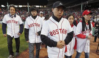 """Family members of Boston Marathon bombing victim Lu Lingzi walk off the field after announcing """"play ball"""" during ceremonies marking the one-year anniversary of the bombings before a baseball game between the Boston Red Sox and the Baltimore Orioles in Boston, Sunday, April 20, 2014. (AP Photo/Michael Dwyer)"""