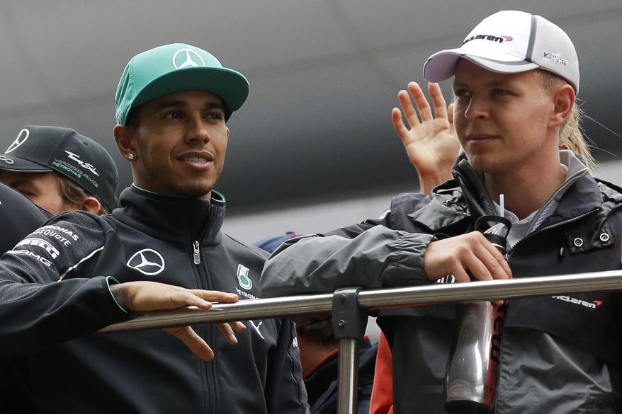 CORRECTS ID OF DRIVER AT RIGHT - Mercedes drivers Lewis Hamilton of Britain, left, and Kevin Magnussen of Denmark stand on a double decker during the driver's parade prior to the start of the Chinese Formula One Grand Prix at Shanghai International Circuit in Shanghai, China, Sunday, April 20, 2014. (AP Photo/Alexander F. Yuan)