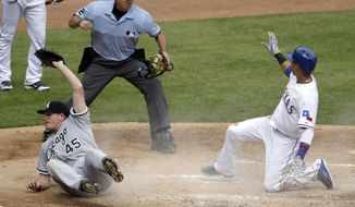 Chicago White Sox starting pitcher Erik Johnson (45) holds up the ball after a collision at home plate as umpire James Hoye rules Texas Rangers' Leonys Martin out at the plate in the third inning of a baseball game, Sunday, April 20, 2014, in Arlington, Texas. Martin was trying to score from third on a wild pitch by Johnson. (AP Photo/Tony Gutierrez)