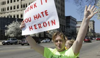 In this April 19, 2014, photo, Candy Murray Abbott waves at passing motorists during an anti-heroin rally held by Heroin Control in Hamilton, Ohio. (AP Photo/Al Behrman)