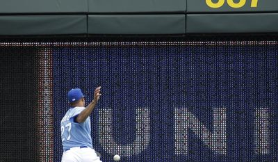 Kansas City Royals right fielder Justin Maxwell chases a two-run double by Minnesota Twins' Trevor Plouffe during the first inning of a baseball game on Sunday, April 20, 2014, at Kauffman Stadium in Kansas City, Mo. (AP Photo/Charlie Riedel)