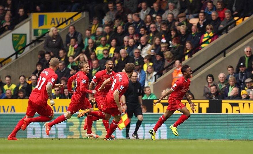 Liverpool's Raheem Sterling, right, celebrates scoring the opening goal during their English Premier League match against Norwich City at Carrow Road, Norwich, eastern England, Sunday April 20, 2014. (AP Photo/PA, Chris Radburn)  UNITED KINGDOM OUT  NO SALES  NO ARCHIVE