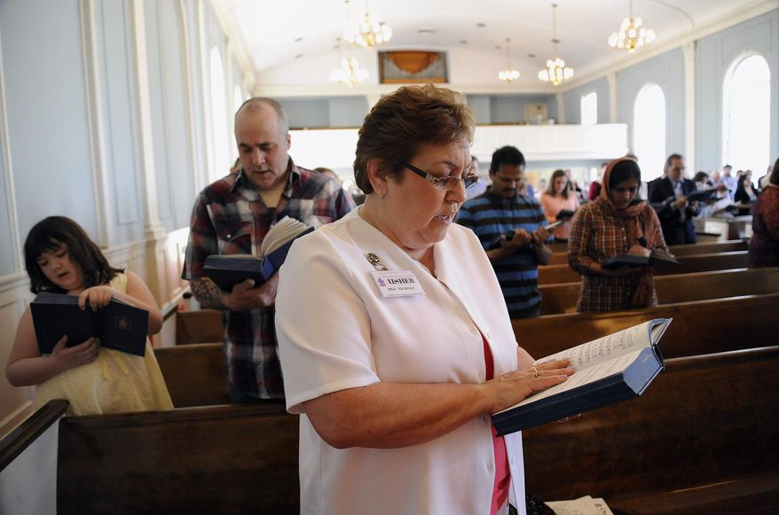 Usher Jill Nichols and the rest of the congregation sing a hymn at the start of a Easter service, Sunday, April 20, 2014, at Cherry Hill Presbyterian Church in Dearborn, Mich. (AP Photo/The Detroit News, Jose Juarez)