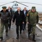 Russian President Vladimir Putin (center) and Defense Minister Sergei Shoigu (left) and the commander of the Western Military District, Anatoly Sidorov arrive to watch military exercises near St. Petersburg. Russia has shown off its new arsenal as it masses near Ukraine. (RIA-Novosti via Associated Press)