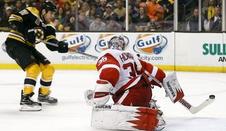 Boston Bruins' Milan Lucic, left, scores on Detroit Red Wings goalie Jimmy Howard during the second period of Game 2 of a first-round NHL hockey playoff series in Boston Sunday, April 20, 2014. (AP Photo/Winslow Townson)