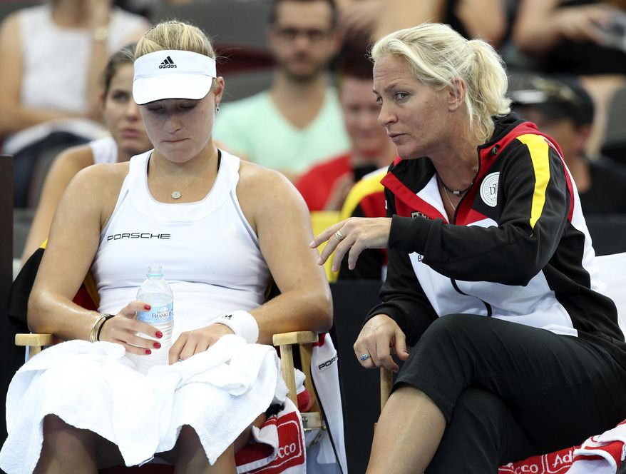 Angelique Kerber of Germany, left, and her team captain Barabara Rittner, right, talk between sets in her match against Samantha Stosur of Australia during the Fed Cup semifinals between Australia and Germany in Brisbane, Australia, Sunday, April 20, 2014. (AP Photo/Tertius Pickard)
