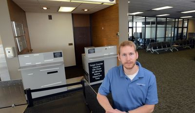 In this April 9, 2014 photo, airport manager Joseph Hedrick stands near the empty Great Lakes Airlines ticket counter at Thief River Falls Regional Airport in Thief River Falls, Minn. Great Lakes, a small regional carrier, suspended its service in February to Thief River Falls, where employees and employers said the air service was a crucial link to the Minneapolis-St. Paul area and beyond. (AP Photo/Jackie Lorentz)