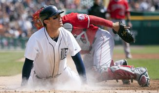 Detroit Tigers' Ian Kinsler, left, looks to the umpire for the call after scoring against Los Angeles Angels catcher Hank Conger on a throwing error by Angels center fielder Mike Trout in the first inning of a baseball game on Sunday, April 20, 2014, in Detroit. The Tigers defeated the Angels 2-1. (AP Photo/Duane Burleson)