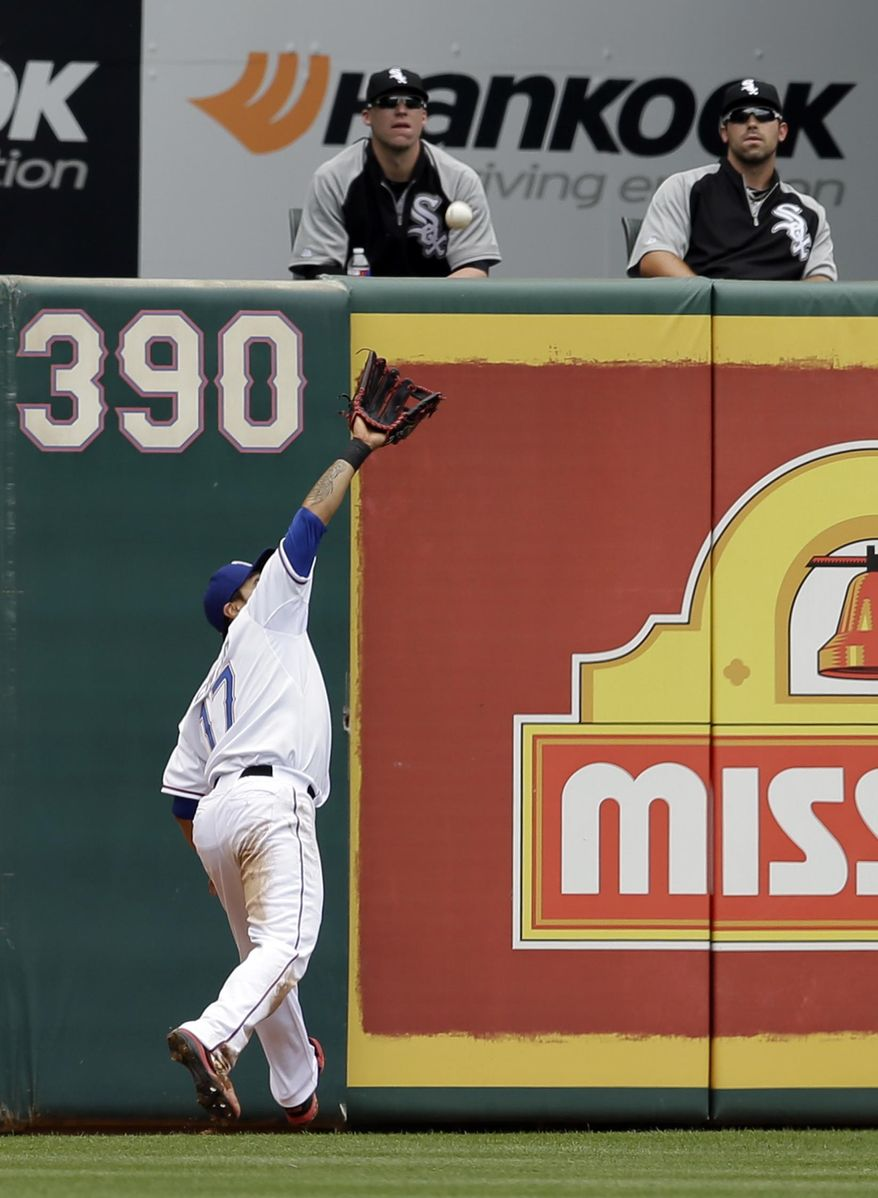 Texas Rangers left fielder Shin-Soo Choo, of South Korea, chases down a fly-out by Chicago White Sox's Adam Dunn as the White Sox bullpen watches in the second inning of a baseball game on Sunday, April 20, 2014, in Arlington, Texas. (AP Photo/Tony Gutierrez)