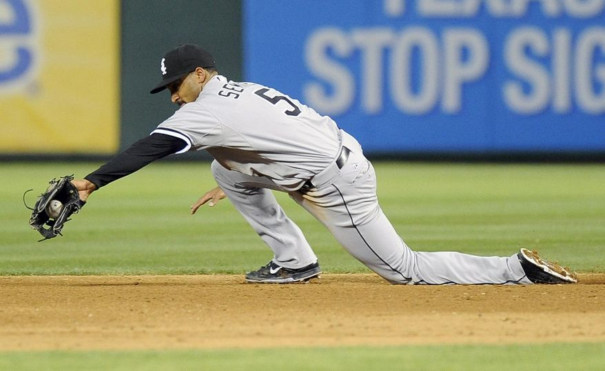 Chicago White Sox second baseman Marcus Semien (5) makes a diving stop in the seventh inning of a baseball game against the Texas Rangers, Saturday, April 19, 2014, in Arlington, Texas. The Texas Rangers won 6-3. (AP Photo/Matt Strasen)