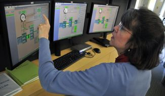 ADVANCE FOR RELEASE MONDAY, APRIL 21, 2014, AT 1:01 A.M. CDT, AND THEREAFTER - In this undated photo, Jami Boettcher looks at information in the operations room at the National Weather Center, in Norman, Okla. Boettcher credits the encouragement of a teacher for expanding her vision of opportunities that would be open to her. Without that encouragement she wouldn't have found her way to a career as a meteorologist with the National Weather Service. (AP Photo/The Norman Transcript, Kyle Phillips)