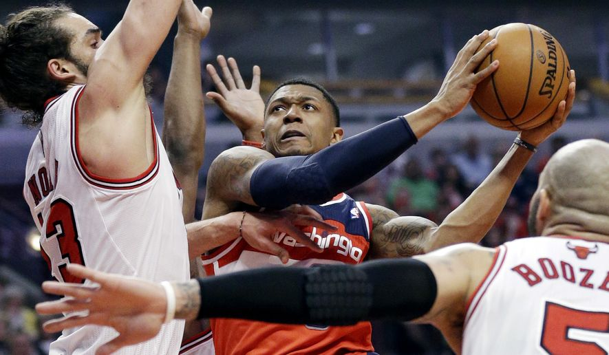 Washington Wizards guard Bradley Beal (3), center, drives to the basket against Chicago Bulls center Joakim Noah, left, and forward Carlos Boozer (5) during the first half in Game 1 of an opening-round NBA basketball playoff series in Chicago, Sunday, April 20, 2014. (AP Photo/Nam Y. Huh)