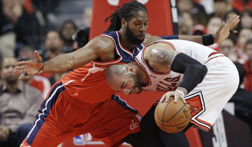 Washington Wizards forward Nene, left, guards Chicago Bulls forward Carlos Boozer during the first half in Game 1 of an opening-round NBA basketball playoff series in Chicago, Sunday, April 20, 2014. (AP Photo/Nam Y. Huh)