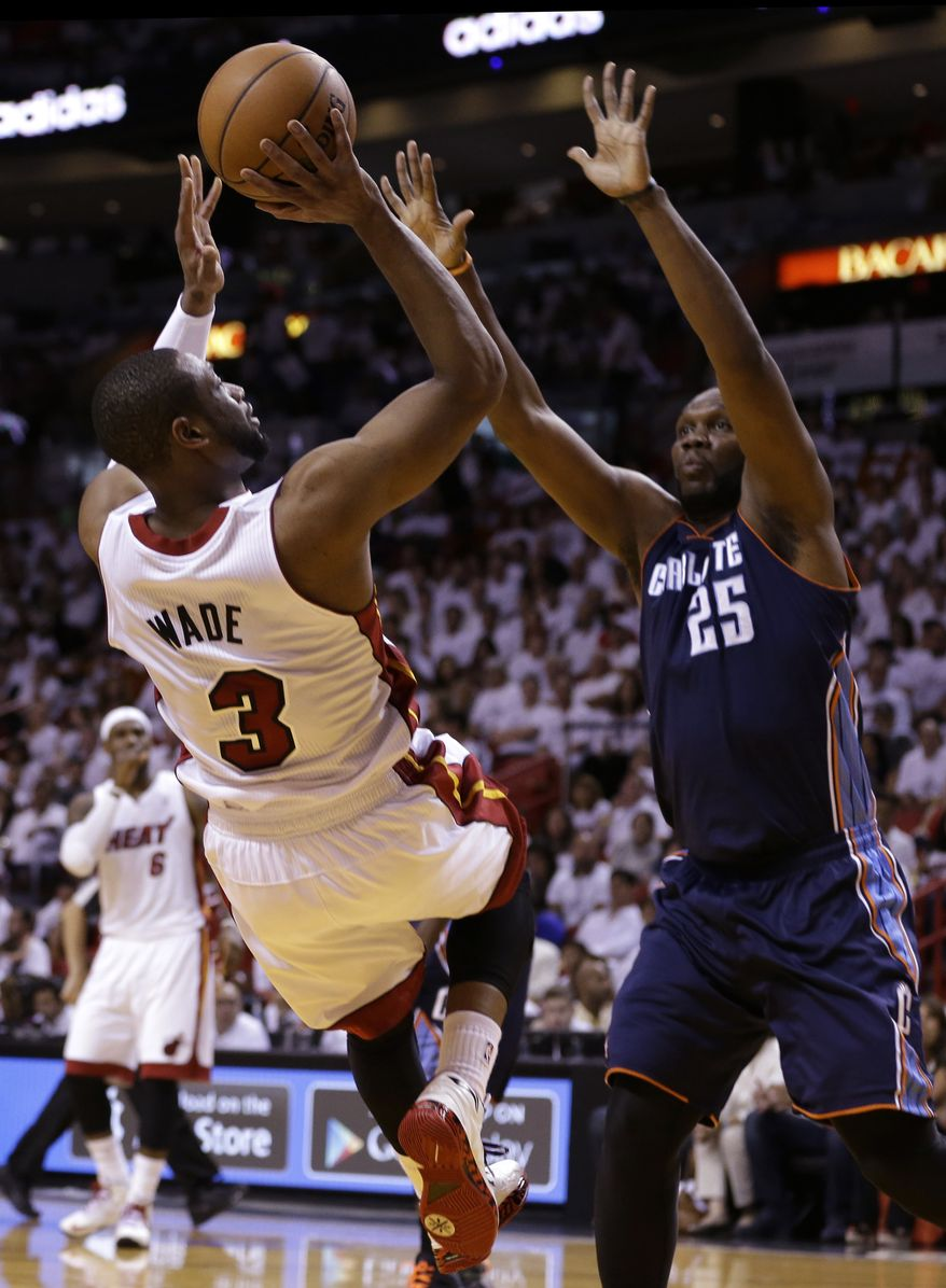 Miami Heat's Dwyane Wade (3) shoots over Charlotte Bobcats' Al Jefferson (25) during the first half in Game 1 of an opening-round NBA basketball playoff series, Sunday, April 20, 2014, in Miami. (AP Photo/Lynne Sladky)