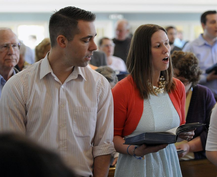 Lauren Russell, right, and her fiancee, Mike Nowacki, sing a hymn at the start of a Easter service, Sunday, April 20, 2014, at Cherry Hill Presbyterian Church in Dearborn, Mich. (AP Photo/The Detroit News, Jose Juarez)