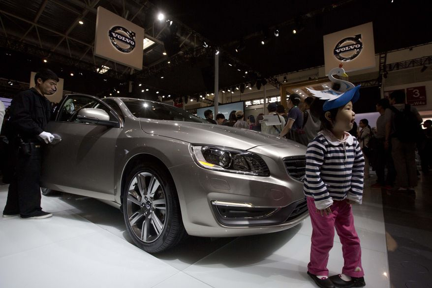 A child poses for photos near a Volvo S60L at the China Auto in Beijing, China, Sunday, April 20, 2014. (AP Photo/Ng Han Guan)