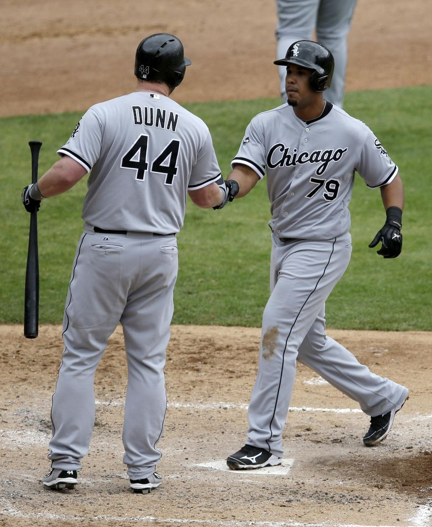 Chicago White Sox's Adam Dunn (44) congratulates Jose Abreu (79) on his two-run home run off a pitch from Texas Rangers starting pitcher Robbie Ross that scored Marcus Semien in the fifth inning of a baseball game, Sunday, April 20, 2014, in Arlington, Texas. (AP Photo/Tony Gutierrez)
