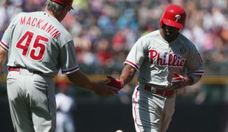 Philadelphia Phillies third base coach Pete Mackanin, left, congratulates Jimmy Rollins who circles the bases after hitting a solo home run against the Colorado Rockies in the first inning of a baseball game in Denver, Sunday, April 20, 2014. (AP Photo/David Zalubowski)