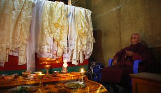 A Buddhist monk performs rituals next to a casket containing the dead body of Nepalese mountaineer Ang Kaji Sherpa, killed in an avalanche on Mount Everest, offer prayers at the Sherpa Monastery in Katmandu, Nepal, Sunday, April 20, 2014. Rescuers were searching through piles of snow and ice on the slopes of Mount Everest on Saturday for four Sherpa guides who were buried by an avalanche that killed 12 other Nepalese guides in the deadliest disaster on the world's highest peak. The Sherpa people are one of the main ethnic groups in Nepal's alpine region, and many make their living as climbing guides on Everest and other Himalayan peaks. (AP Photo/Niranjan Shrestha)