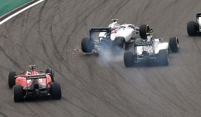 Williams driver Felipe Massa of Brazil, center left, and Mercedes driver Nico Rosberg of Germany, right, collide into turn one at the start of the Chinese Formula One Grand Prix at Shanghai International Circuit in Shanghai, Sunday, April 20, 2014. (AP Photo/Eugene Hoshiko)