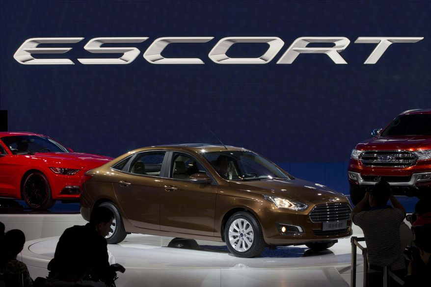 The Ford Escort sedan is unveiled during press day at the China Auto show in Beijing, China, Sunday, April 20, 2014. Ford Motor Co. on Sunday unveiled a new Escort sedan designed in China for global sale at a Beijing auto show that highlighted the growing influence of Chinese tastes on the industry. (AP Photo/Ng Han Guan)