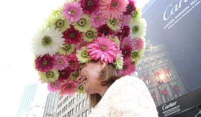 Dressed for the occasion, Michelle White poses for photographs as she makes her way along New York's Fifth Avenue during the Easter Parade, Sunday, April 20, 2014. (AP Photo/Tina Fineberg)