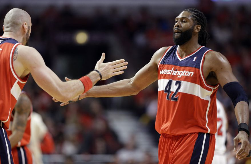 Washington Wizards forward Nene, right, celebrates with center Marcin Gortat after scoring  basket against the Chicago Bulls during the second half in Game 1 of an opening-round NBA basketball playoff series in Chicago, Sunday, April 20, 2014. The Wizards won 102-93. (AP Photo/Nam Y. Huh)
