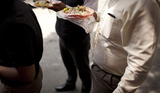 FILE - In this July 10, 2013, file photo, office workers eats tacos at an outdoor food stand during lunch time in Mexico City. Mexico has surpassed the United States in levels of adult obesity. Mexico's new food labeling rules were supposed to help fight an obesity epidemic, but activists and experts said Monday, april 21, 2014, that they may actually encourage the public to consume high levels of sugar. (AP Photo/Ivan Pierre Aguirre,File)