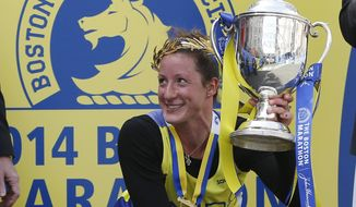 Tatyana McFadden, of the United States, displays her trophy after winning the women's wheelchair division of the 118th Boston Marathon Monday, April 21, 2014 in Boston. (AP Photo/Elise Amendola)
