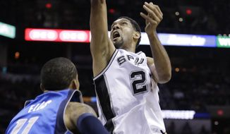 San Antonio Spurs' Tim Duncan (21) shoots over Dallas Mavericks' Monta Ellis (11) during the first quarter of Game 1 of the opening-round NBA basketball playoff series on Sunday, April 20, 2014, in San Antonio. (AP Photo/Eric Gay)