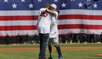 Boston Marathon bombing survivor Marc Fucarile hugs former Red Sox player Kevin Millar after throwing out the ceremonial first pitch before the baseball game between the Boston Red Sox and the Baltimore Orioles at Fenway Park in Boston Monday, April 21, 2014. (AP Photo/Winslow Townson)