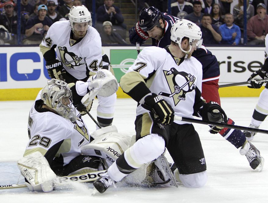 Pittsburgh Penguins' Marc-Andre Fleury, front left, covers the puck as teammates Brooks Orpik, left, Paul Martin, front right, and Columbus Blue Jackets' Brandon Dubinsky look for the rebound during the second period of a first-round NHL playoff hockey game Monday, April 21, 2014, in Columbus, Ohio. (AP Photo/Jay LaPrete)