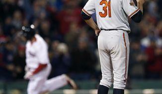 Baltimore Orioles' Ubaldo Jimenez (31) looks to the outfield as Boston Red Sox's Jonny Gomes (5), left, rounds third base on a three-run home run in the sixth inning of a baseball game in Boston, Sunday, April 20, 2014. (AP Photo/Michael Dwyer)