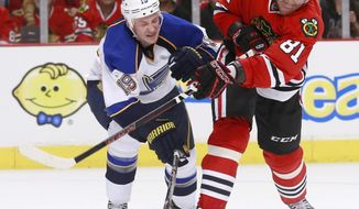St. Louis Blues defenseman Jay Bouwmeester (19) deflects a shot by Chicago Blackhawks right wing Marian Hossa (81) during the second period in Game 3 of a first-round NHL hockey Stanley Cup playoff series game Monday, April 21, 2014, in Chicago. (AP Photo/Charles Rex Arbogast)