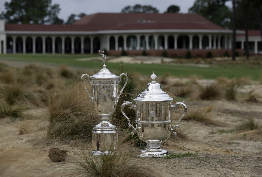 The men's and women's U.S. Open Championship trophies are shown along the 18th fairway at Pinehurst Resort & Country Club's Course No. 2 in Pinehurst, N.C., Monday, April 14, 2014. The No. 2 course will host the 2014 U.S. Open Championship June 12-15 and the 2014 U.S. Women's Open Championship June 19-22. (AP Photo/Gerry Broome)