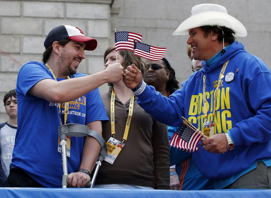 Holding American flags, Boston Marathon bombing survivor Jeff Bauman, left, bumps fists with Carlos Arredondo near the finish line of the the 118th Boston Marathon, Monday, April 21, 2014, in Boston. (AP Photo/Elise Amendola)