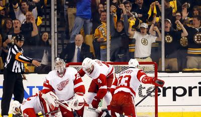 Boston fans cheer while Detroit Red Wings, left to right, Kyle Quincey, Jimmy Howard, Jakub Kindl, and Brian Lashoff slump in the crease after Boston Bruins' Reilly Smith scored during the first period of Boston's 4-1 win in Game 2 of a first-round NHL hockey playoff series in Boston Sunday, April 20, 2014. (AP Photo/Winslow Townson)