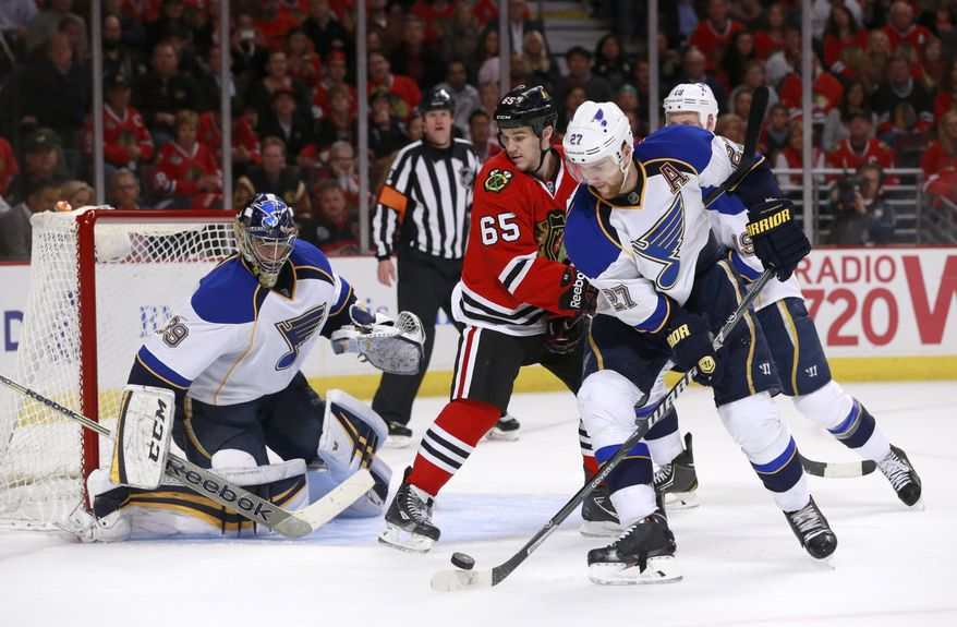 St. Louis Blues defenseman Alex Pietrangelo (27) clears the puck away from the net and Chicago Blackhawks center Andrew Shaw (65) as goalie Ryan Miller defends during the second period in Game 3 of a first-round NHL hockey Stanley Cup playoff series game Monday, April 21, 2014, in Chicago. (AP Photo/Charles Rex Arbogast)