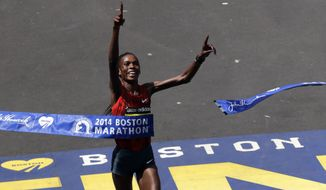 Rita Jeptoo, of Kenya, bereaks the tape to win the women's division of the 118th Boston Marathon Monday, April 21, 2014 in Boston. (AP Photo/Charles Krupa)