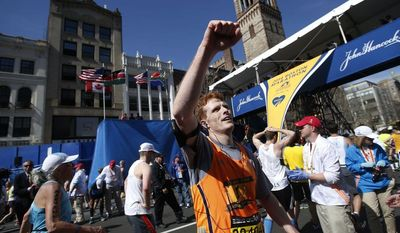 U.S. Rep. Joseph Kennedy, D-Mass., waves to race fans after completing the 118th Boston Marathon Monday, April 21, 2014 in Boston. (AP Photo/Elise Amendola)