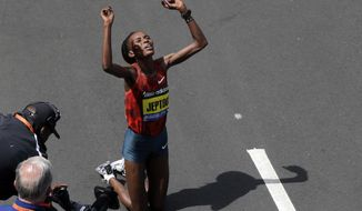 Rita Jeptoo, of Kenya,  celebrates her win in the women's division of the 118th Boston Marathon Monday, April 21, 2014 in Boston. (AP Photo/Charles Krupa)