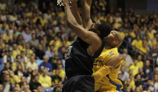 Emporio Armani Milan's Gani Lawal of USA, left, goes for the basket past Maccbi Tel Aviv's Alex Tyus during EuroLeague Basketball Group D playoffs game in Tel Aviv, Israel, Monday, April 21, 2014. (AP Photo/Ariel Schalit)