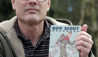 FILE - In this Tuesday, April 1, 2014, file photo, Geoff McGrath displays a vintage Boy Scout Handbook given him as a gift by one of the boys in the Seattle troop he led in Bellevue, Wash. The Boys Scouts of America has revoked the charter of a Seattle church because it allowed a gay adult to continue leading a troop. A Boys Scouts of America attorney told Rainier Beach United Methodist Church last week that it could no longer hosts troops under the Boys Scout name. McGrath, who earned the rank of Eagle Scout, has been leading Seattle Troop 98 since its application was approved last fall. (AP Photo/Elaine Thompson, File)