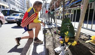 ** FILE ** Ron McCracken of Dallas pays his respects at a makeshift memorial honoring to the victims of the 2013 Boston Marathon bombings ahead of Monday's 118th Boston Marathon, Sunday, April 20, 2014, in Boston. McCracken's race last year was cut short due to bombings and Monday's race will mark his 14th year running in the Boston Marathon.  The memorial is where the second of two explosions happened last year near the finish line. (AP Photo/Matt Rourke)