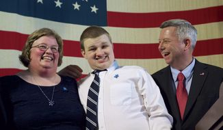 Nebraska Governor Dave Heineman, right, laughs as he poses for a photo with Jacob Depenbusch of Lincoln, 15, and his mother Vicki Depenbusch, in Lincoln, Neb., Monday, April 21, 2014 after signing a bill into law that would require insurance companies to cover autism therapy,. (AP Photo/Nati Harnik)